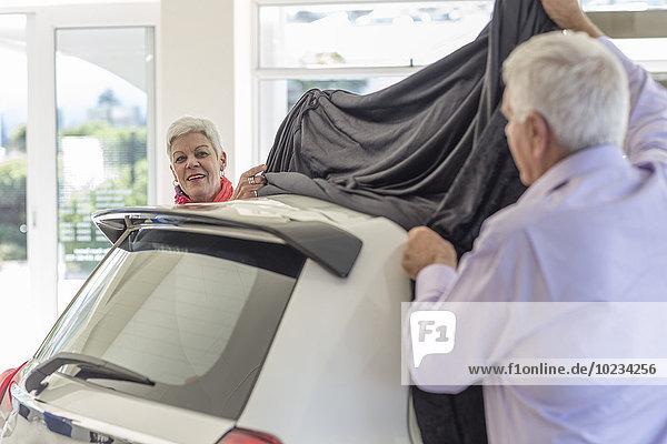 Seniorenpaar enthüllt ein neues Auto beim Autohändler