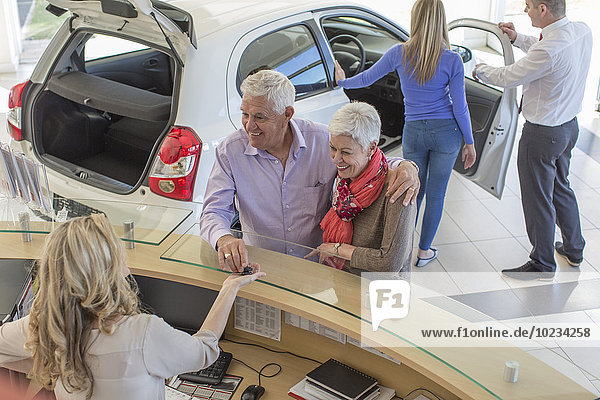 Menschen bei einem Autohändler im Showroom