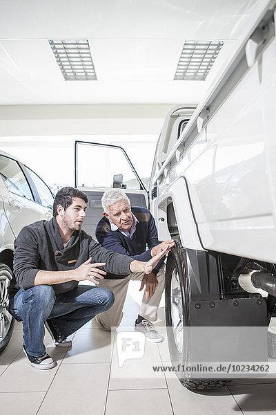 Zwei Männer beim Autohändler  die den Pick-Up untersuchen.