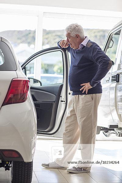 Senior Mann auf der Suche nach einem neuen Auto im Showroom