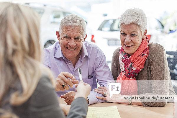 Lächelndes Seniorenpaar beim Autohändler