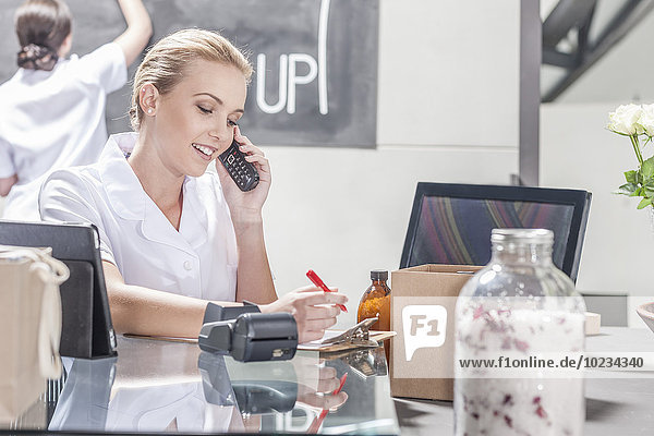 Verkäuferin am Telefon im Wellness-Shop
