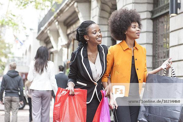 Zwei junge Frauen Arm in Arm beim Einkaufen