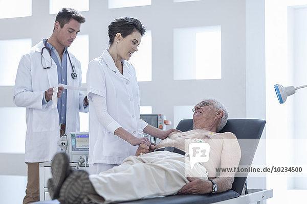 Ein älterer Mann  der im Krankenhaus nachsieht  eine Krankenschwester  die ihn beruhigt.