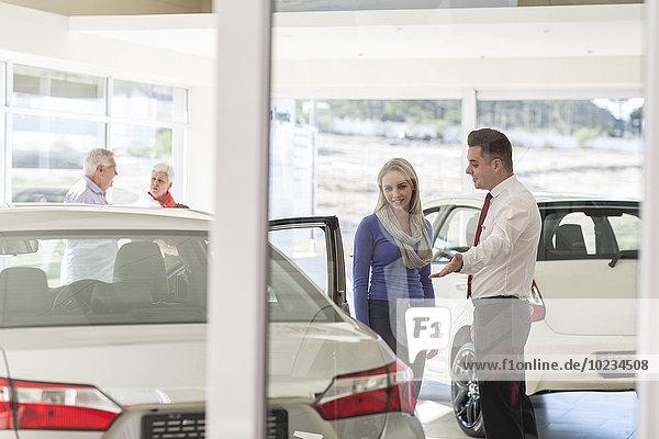 Autohändler im Gespräch mit Frau im Showroom