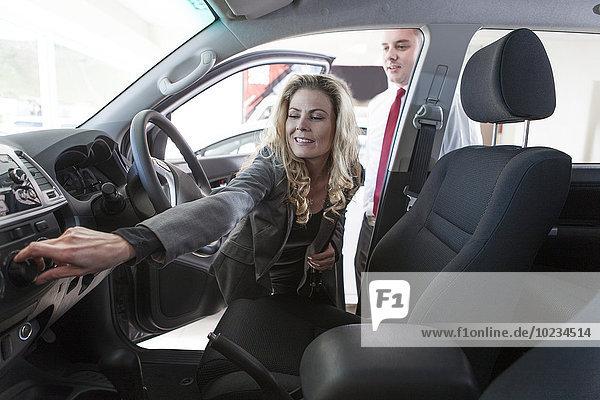 Autohändler zeigt Neuwagen der Frau im Showroom