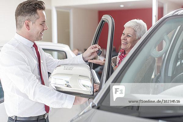 Autohändler übergibt Schlüssel an Seniorin