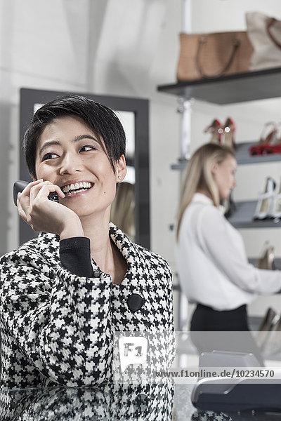 Verkäuferin im Schuhgeschäft am Telefon