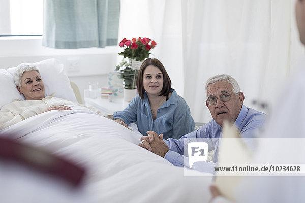 Familie besucht ältere Patientin und sucht Arzt im Krankenhaus