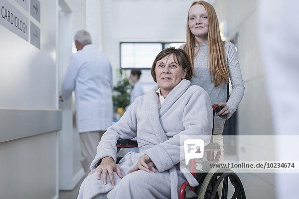 Patientin im Rollstuhl und Enkelin im Krankenhausgang