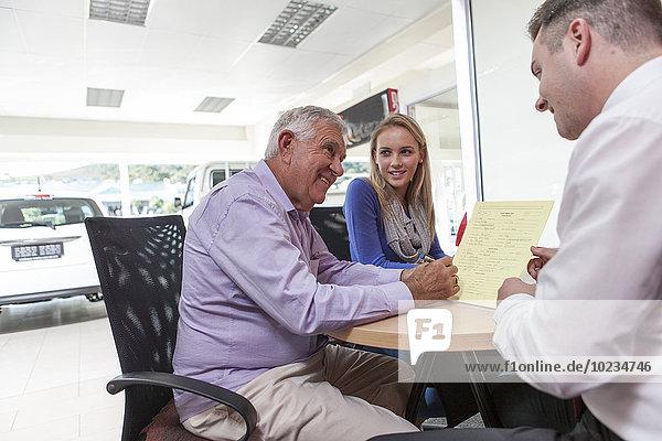 Autohändler im Gespräch mit Kunden am Tisch