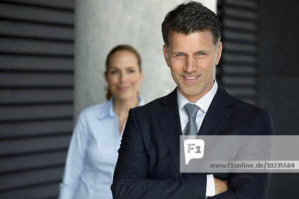 Portrait eines erfolgreichen Geschäftsmannes mit Kollegen im Hintergrund