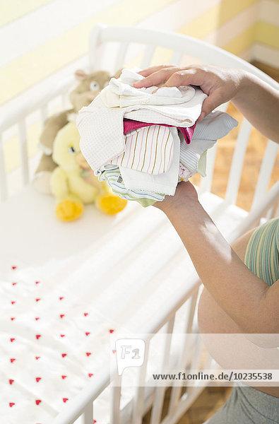 Schwangere Frau mit einem Stapel Babykleidung Schwangere Frau mit einem Stapel Babykleidung