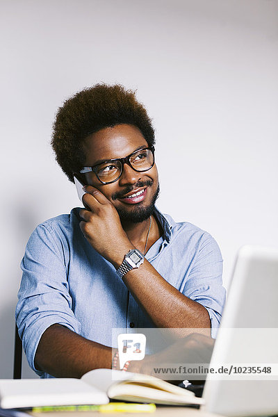 Junger Mann im Home-Office am Telefon