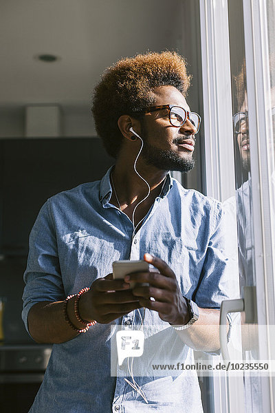 Young man listening to music from smartphone looking out of the window