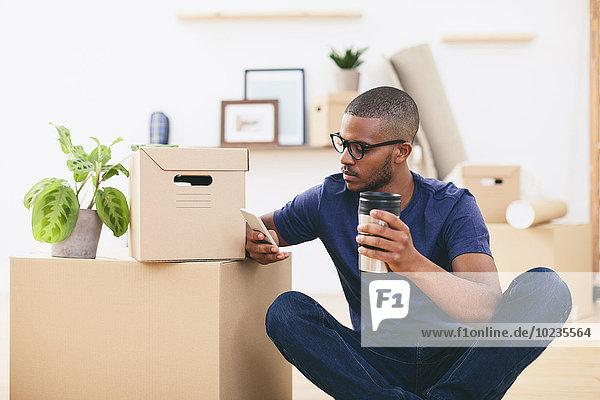 Junger Mann sitzt neben Pappkartons und macht eine Kaffeepause.