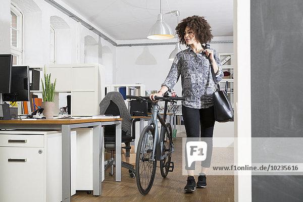 Junge Frau schiebt Fahrrad im Büro