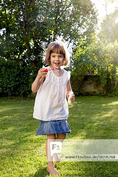 Little girl playing with soap bubbles in a garden