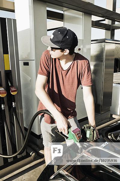 Teenager an der Tankstelle tankt Cabriolet