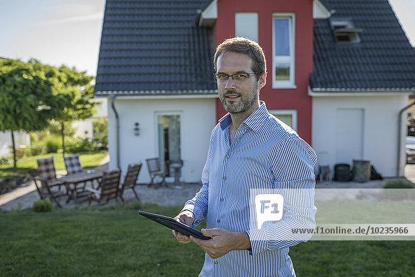 Porträt eines Mannes mit digitalem Tablett vor seinem Einfamilienhaus
