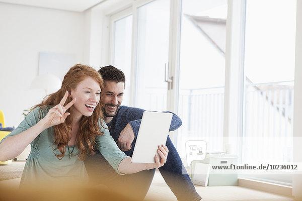 Lächelndes junges Paar  das einen Selfie mit digitalem Tablett im Wohnzimmer nimmt