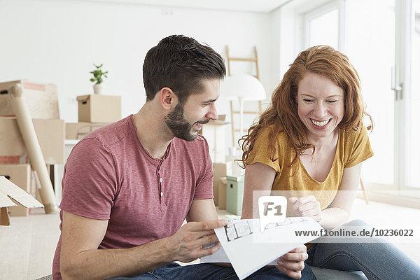 Junges Paar in neuer Wohnung mit Kartonagen im Grundriss