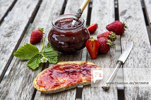 Erdbeermarmelade im Glas  Erdbeeren und Brot mit Marmelade auf Holz