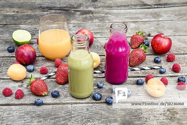 Verschiedene Fruchtsmoothies und Früchte