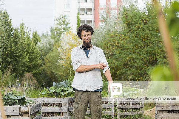 Young man standing in an urban garden