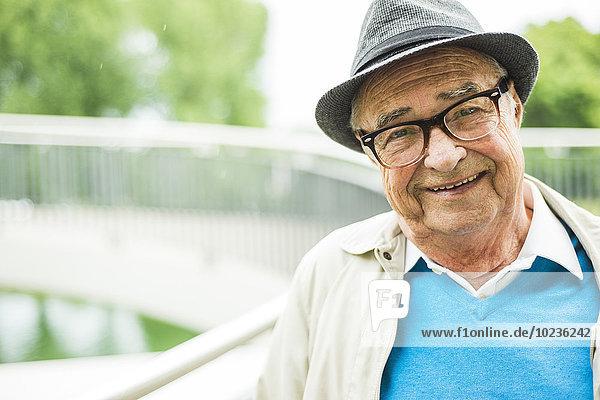 Porträt eines lächelnden älteren Mannes mit Brille und Hut