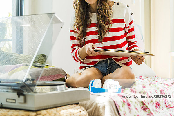 Junge Frau auf dem Bett sitzend mit Schallplatte und Plattenspieler