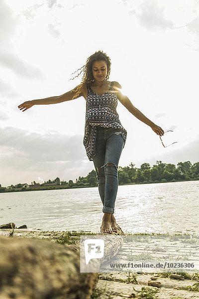 Junge Frau beim Balancieren auf dem Baumstamm am Flussufer