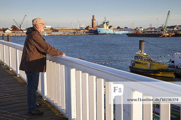 Deutschland  Niedersachsen  Cuxhaven  Senior am Hafen mit Blick auf den Hafen