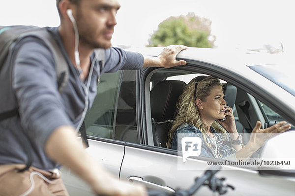 Mann auf dem Fahrrad und Frau im Auto im Stau