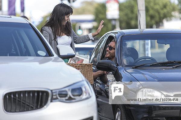 Frau auf dem Fahrrad im Gespräch mit Mann im Auto