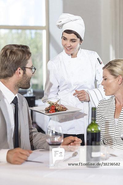 Chefkoch serviert Essen für erwachsene Paare