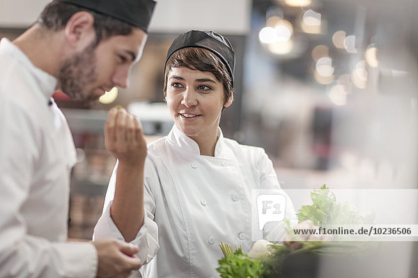 Koch und Köchin mit frischen Zutaten in der Restaurantküche