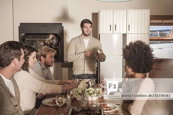 Young man making a speech to friends at dinner table