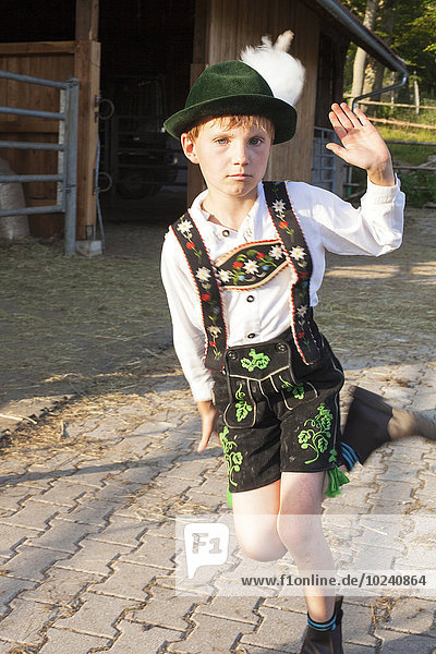 Boy in traditional Bavarian costume running and gesturing