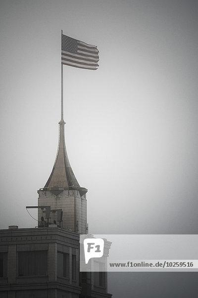 Amerikanische Flagge auf dem Gebäude gegen den klaren Himmel