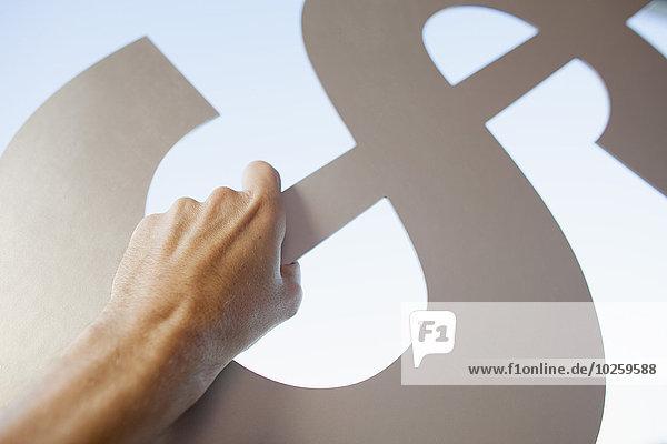 Abgeschnittenes Bild der Hand  die das Dollarzeichen gegen den Himmel hält.