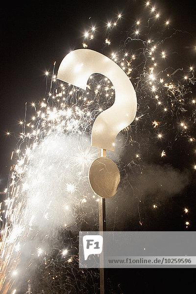 Fragezeichen am Mast mit Feuerwerk bei Nacht