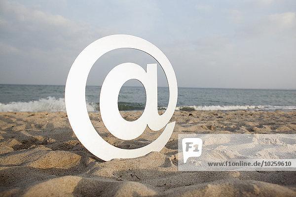 Bei Symbol auf Sand am Strand gegen den Himmel