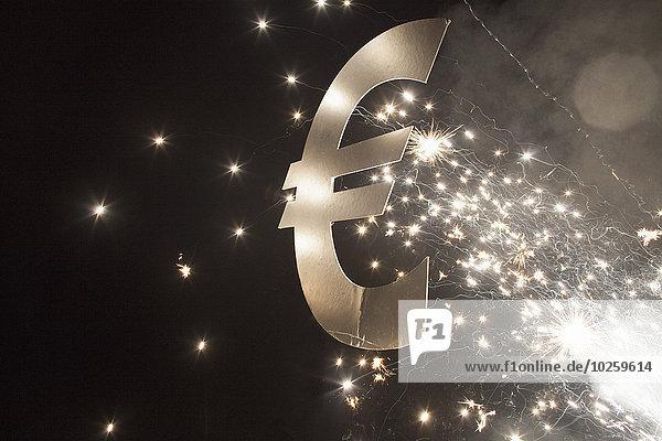 Beleuchtetes Eurosymbol mit Feuerwerk bei Nacht