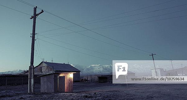 Strommast und Häuser gegen den Himmel in der Dämmerung  Kirgisistan
