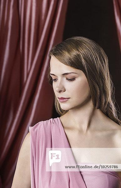 Schöne junge Frau vor dem Vorhang
