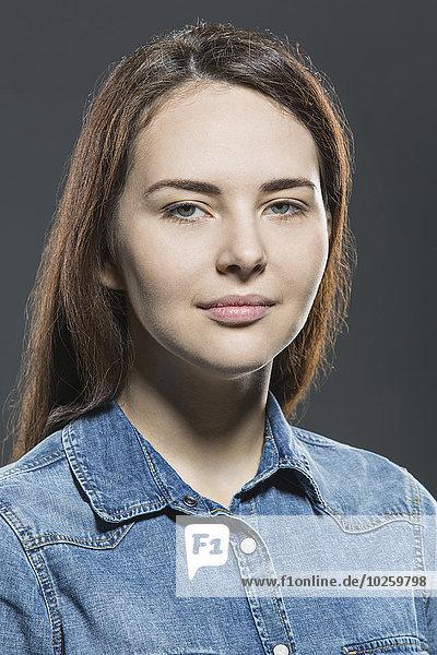 Porträt einer schönen jungen Frau mit Jeansjacke über grauem Hintergrund