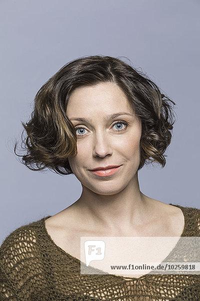 Porträt einer selbstbewussten mittleren erwachsenen Frau über grauem Hintergrund