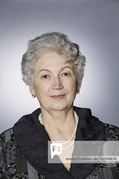 Porträt einer selbstbewussten Seniorin über grauem Hintergrund