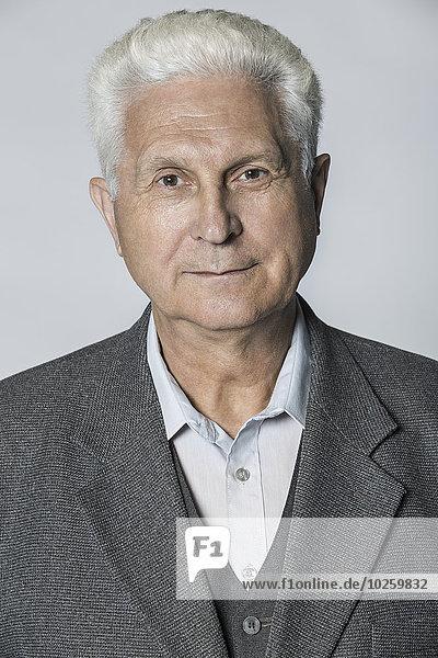 Porträt eines selbstbewussten älteren Mannes über grauem Hintergrund